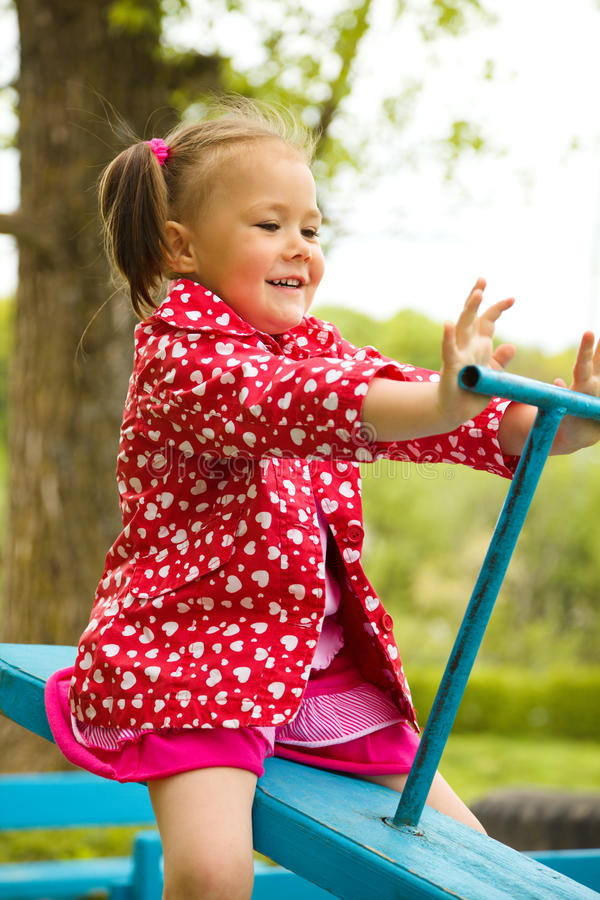 Cute Little Girl Is Swinging On See-saw Royalty Free Stock Image