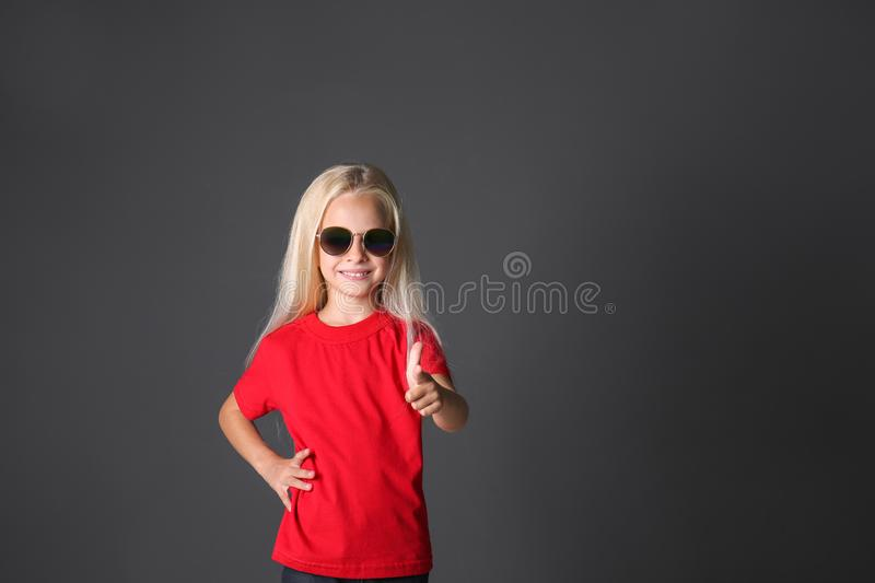 Cute little girl in t-shirt  pointing at viewer on dark background stock photo