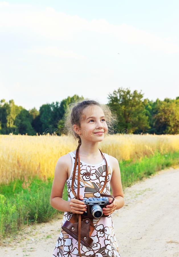 Cute little girl taking pictures with old film camera. Pretty c stock photo