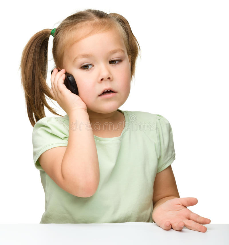 Cute little girl is talking on a cell phone. While sitting at table, isolated over white stock images