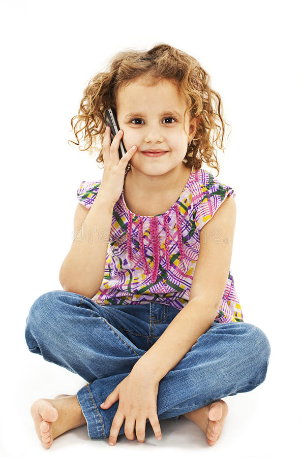 Cute little girl is talking on cell phone. Isolated on white background royalty free stock photography