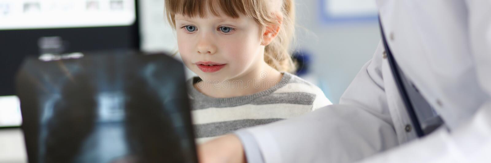 Cute little girl talking with gp looking at xray picture during consultation royalty free stock photos