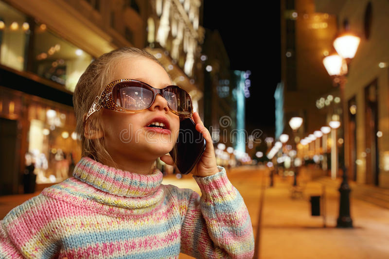 Cute little girl talks on phone. Cute little girl in sunglasses talks on phone in the street at night royalty free stock images