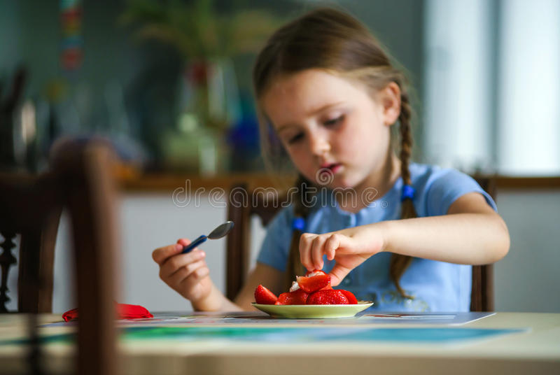 Cute little girl tasting strawberry at home stock image