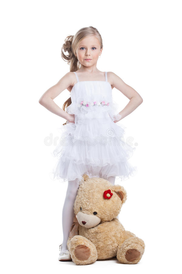Cute little girl with teddy bear posing in studio stock photography