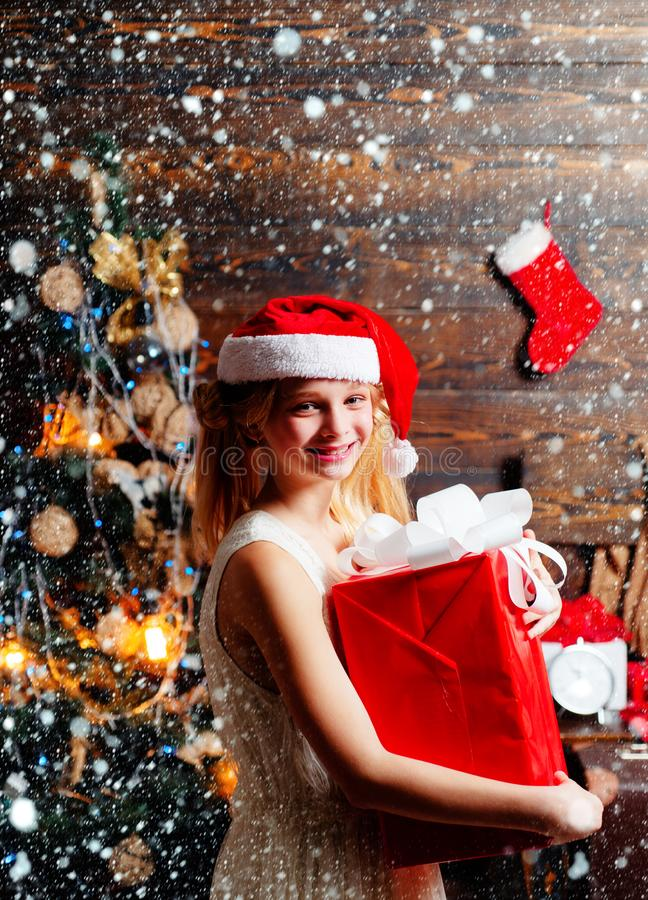 Cute little girl teenager is decorating the Christmas tree indoors. Christmas kids. Portrait of happy Little girl royalty free stock image
