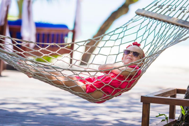 Cute little girl on tropical vacation relaxing in. Adorable little girl on summer vacation relaxing in hammock royalty free stock photos