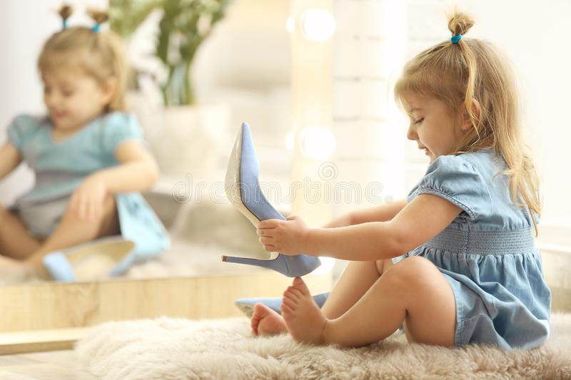 Cute little girl trying on big high heeled shoes. At home royalty free stock images