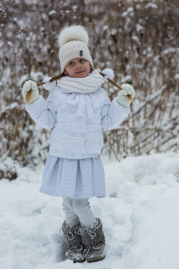 Cute little girl with two braids walking snowy day in the park in a white dress royalty free stock photo