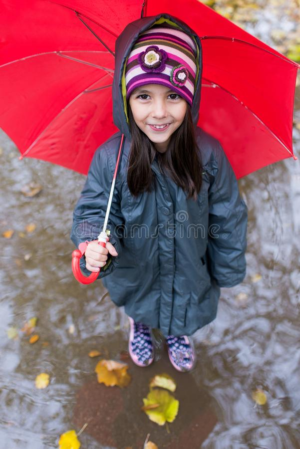 Little girl with umbrella at the rainy day royalty free stock photo