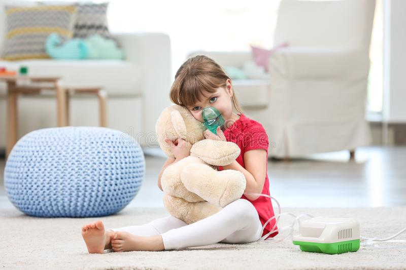Cute little girl using asthma nebulizer at home. Allergy concept royalty free stock image