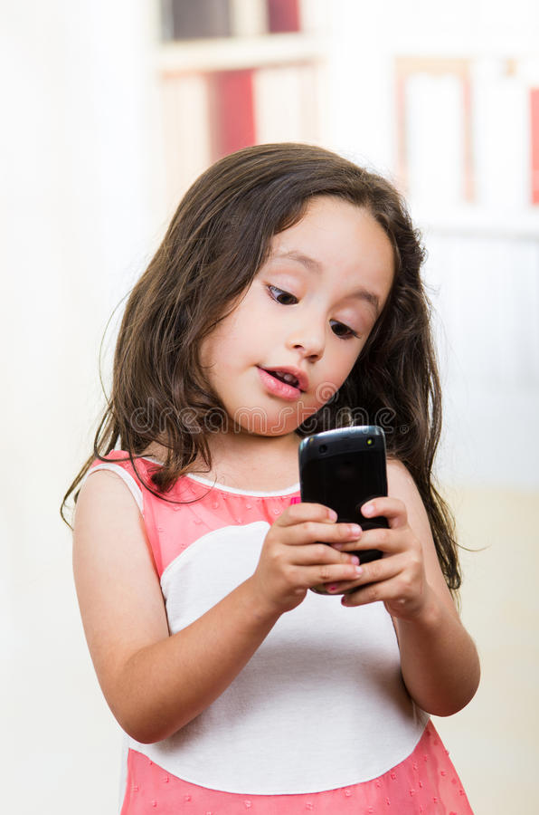 Cute little girl using cell phone. Portrait of cute little happy girl using cell phone texting royalty free stock photos