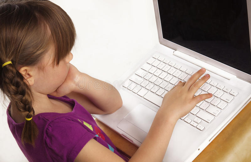 Cute little girl using laptop computer royalty free stock photography