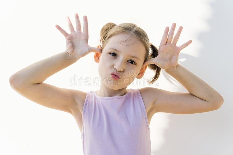 Cute little girl in violet dress make faces against white concrete wall. Joy, childhood royalty free stock images