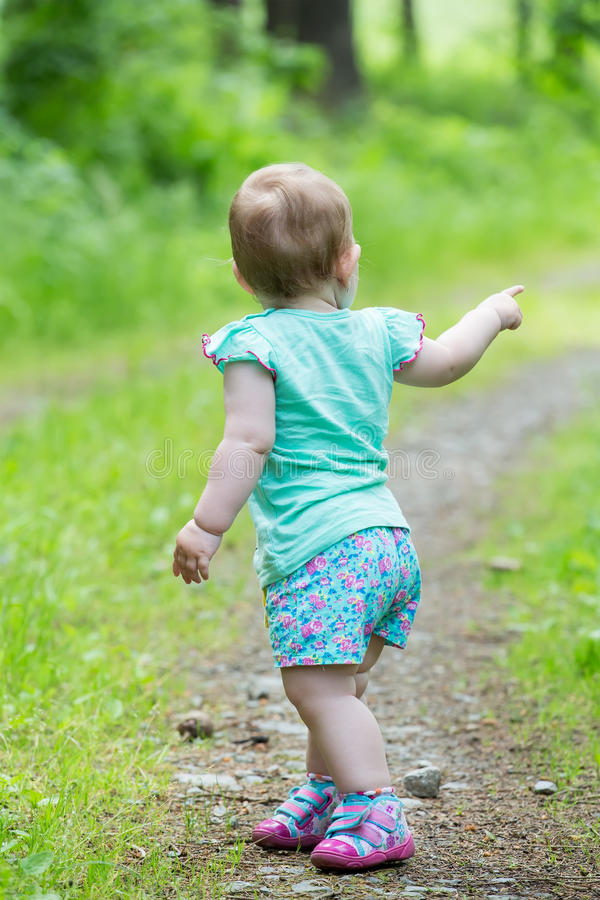 Cute Little girl walking away on the road ahead. Looking back stock photos