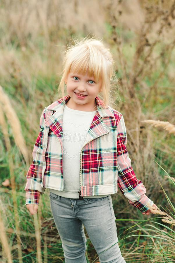 Cute little girl walking at countryside. Fashionable little girl with blue eyes and blondy hair. Kids fashion. Happy child at stock photo