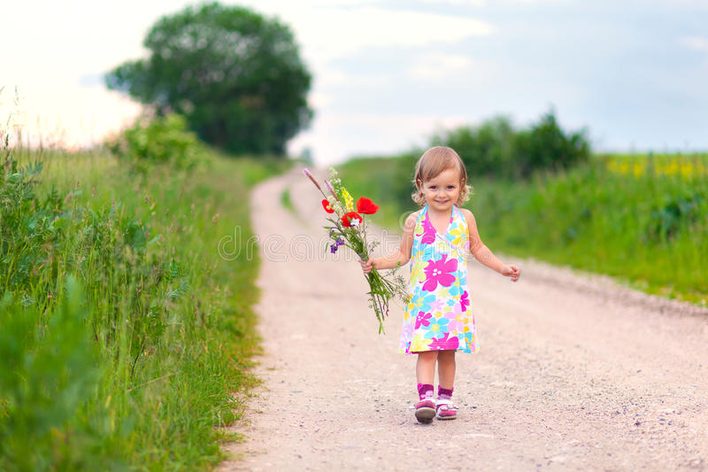 Cute little girl walking on the road. With bouquet of flowers royalty free stock photo