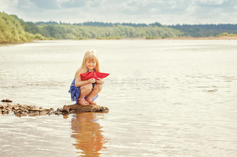 Cute little girl wants to run paper boat in lake. Charming little girl wants to run paper boat in lake royalty free stock images
