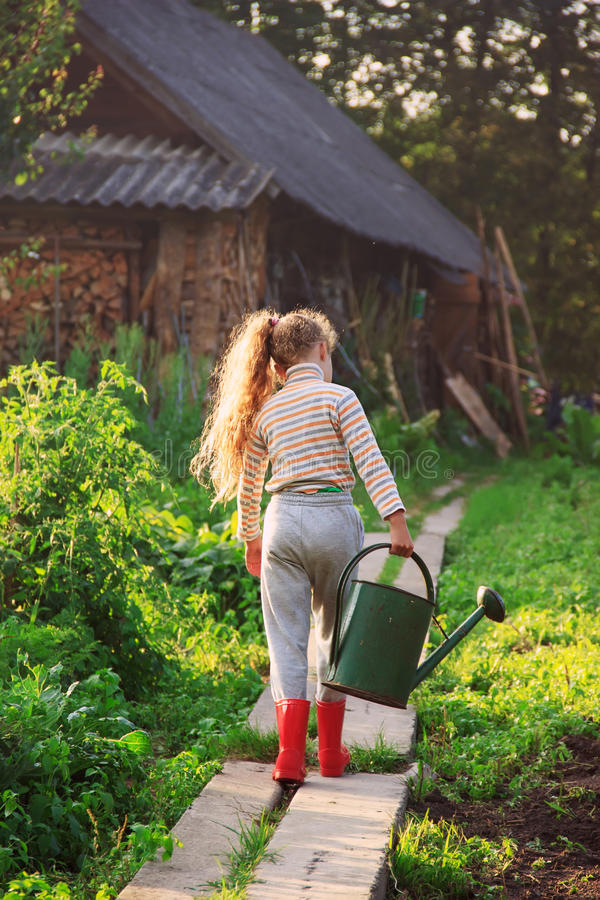 cute little girl watering plants with watering can in garden c stock photo image 88811034. Black Bedroom Furniture Sets. Home Design Ideas