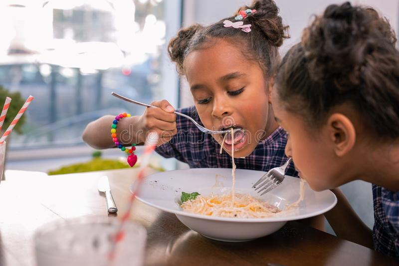 Cute little girl wearing bright bracelet holding fork and eating pasta stock photo