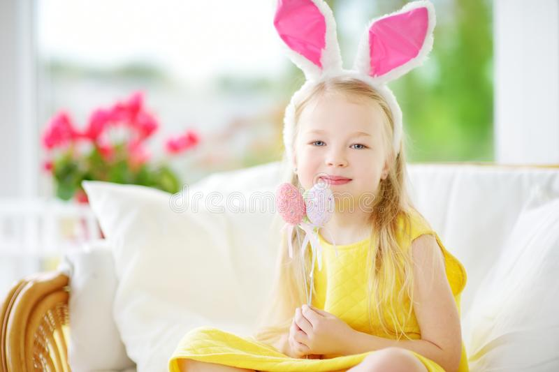 Cute little girl wearing bunny ears playing egg hunt on Easter. Adorable child celebrate Easter at home stock photo