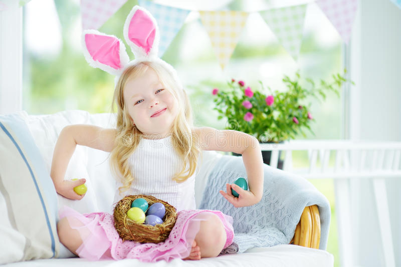 Cute little girl wearing bunny ears playing egg hunt on Easter. Adorable child celebrate Easter at home royalty free stock images