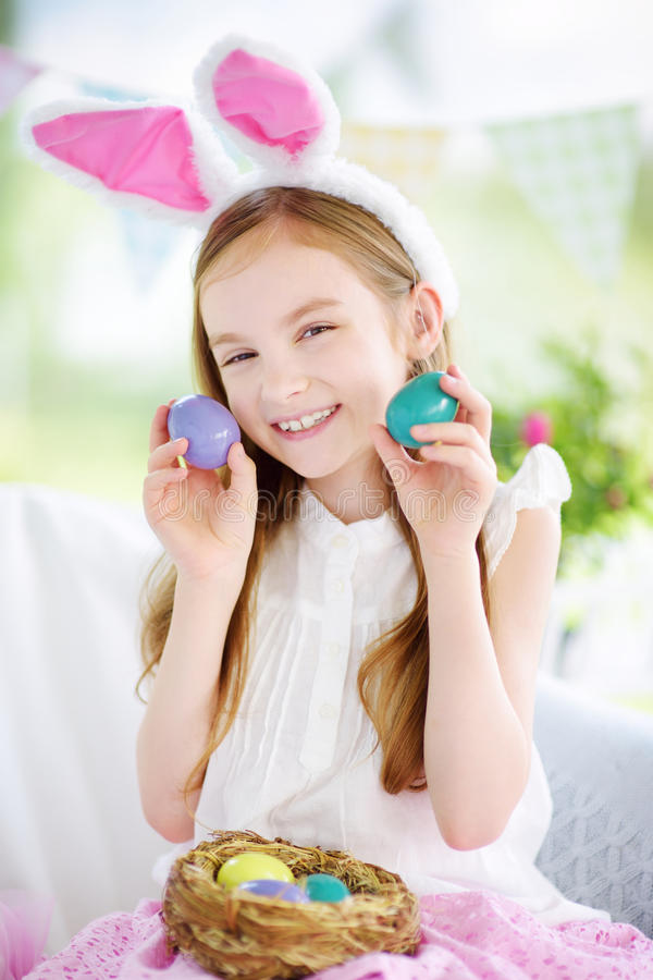 Cute little girl wearing bunny ears playing egg hunt on Easter. Adorable child celebrate Easter at home stock images