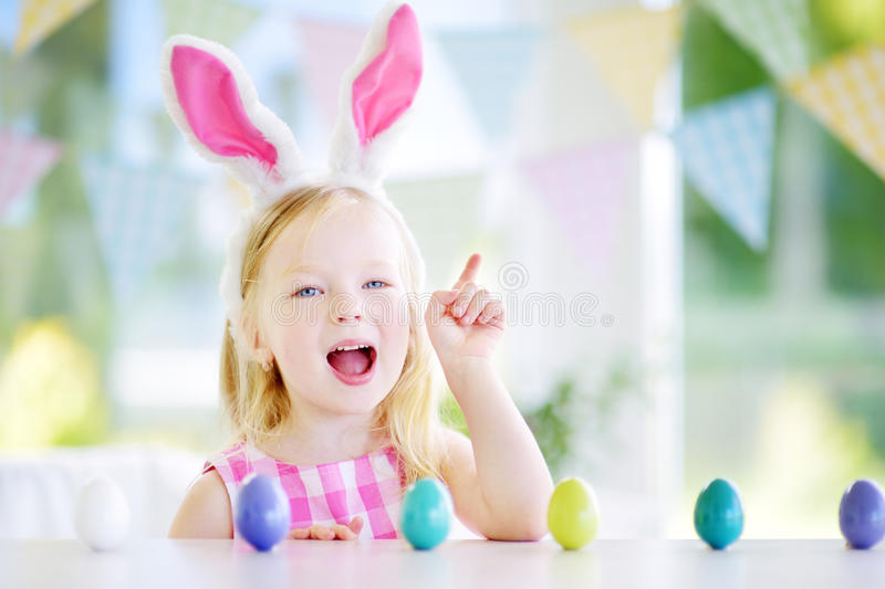 Cute little girl wearing bunny ears playing egg hunt on Easter. Adorable child celebrate Easter at home stock photography
