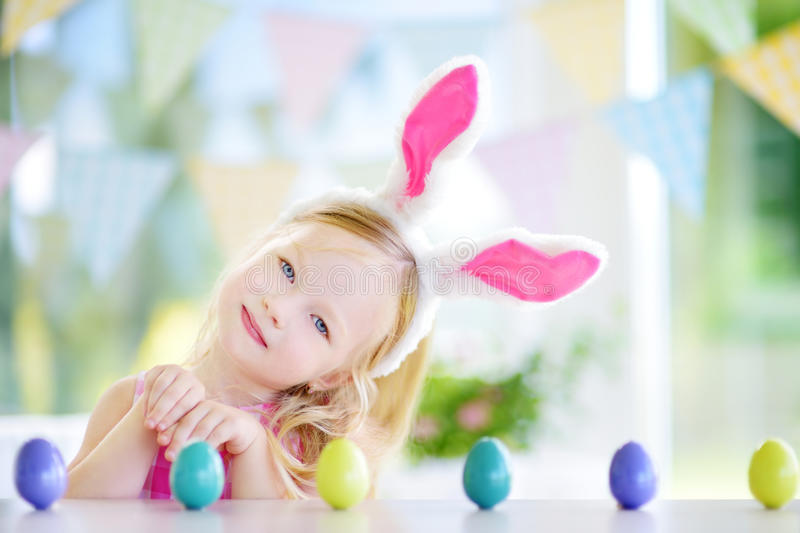 Cute little girl wearing bunny ears playing egg hunt on Easter. Adorable child celebrate Easter at home stock photos