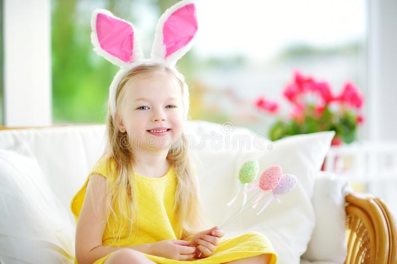 Cute little girl wearing bunny ears playing egg hunt on Easter. Adorable child celebrate Easter at home stock image