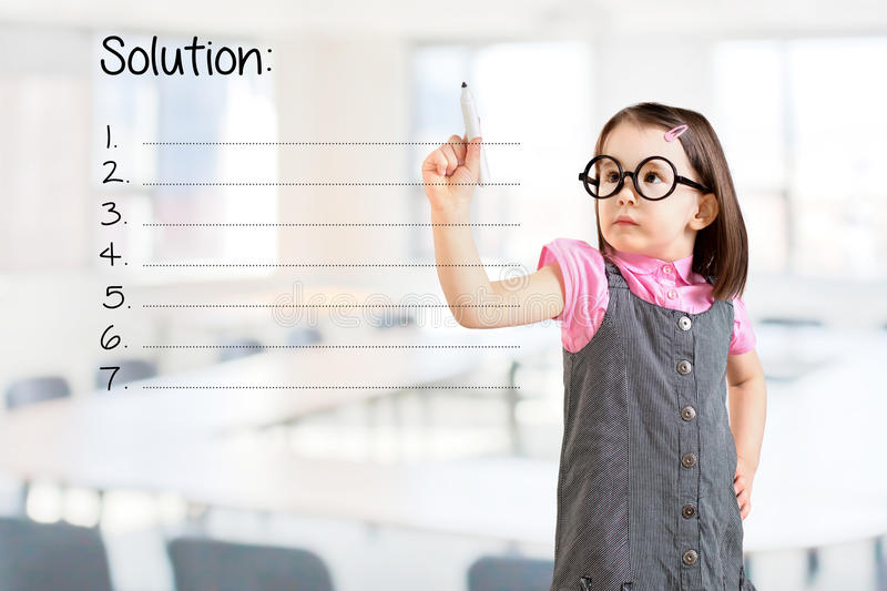 Cute little girl wearing business dress and writing blank solution list. Office background. Cute little girl wearing business dress and writing blank solution stock photography