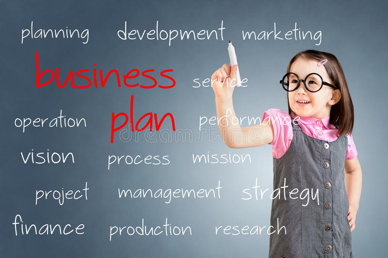 Cute little girl wearing business dress and writing business plan concept. Blue background. Cute little girl wearing business dress and writing business plan royalty free stock images