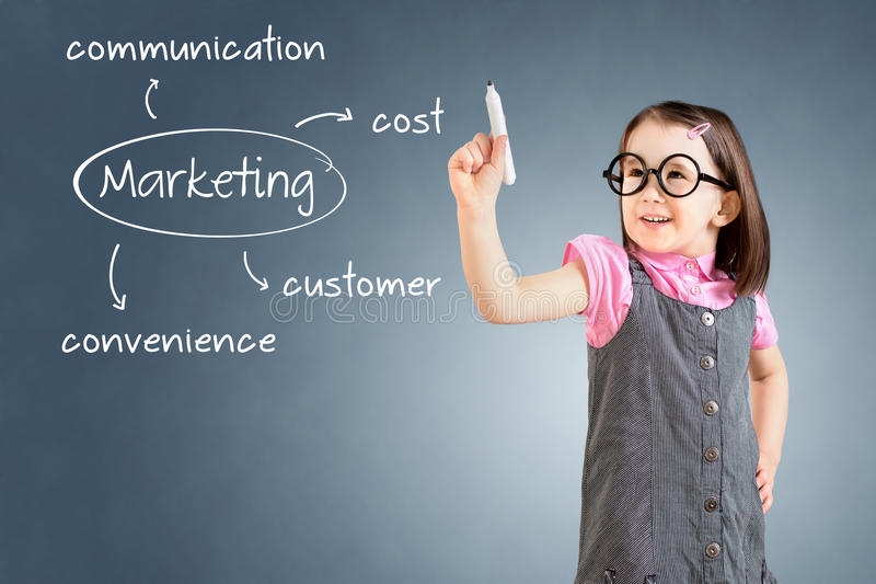 Cute little girl wearing business dress and writing marketing concept - customer, cost, convenience, communication. Blue backgroun. D royalty free stock image