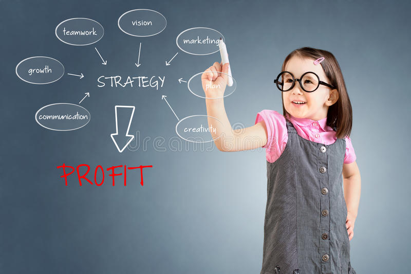 Cute little girl wearing business dress and writing a schema at the whiteboard with ideas for a good strategy to make profit. Blue. Background stock photos
