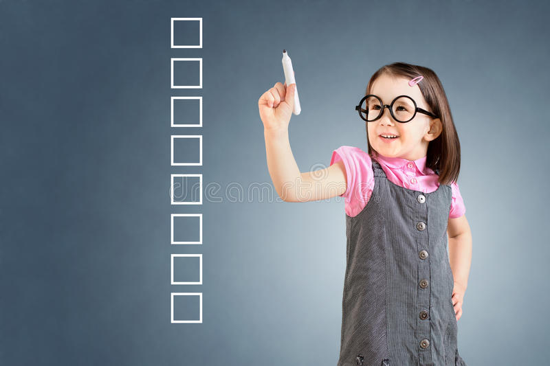 Cute little girl wearing business dress and writing on some blank checklist boxes. Blue background. Cute little girl wearing business dress and writing on some stock image