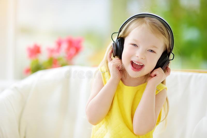 Cute little girl wearing huge wireless headphones. Pretty child listening to the music. Schoolgirl having fun listening to kid`s royalty free stock image