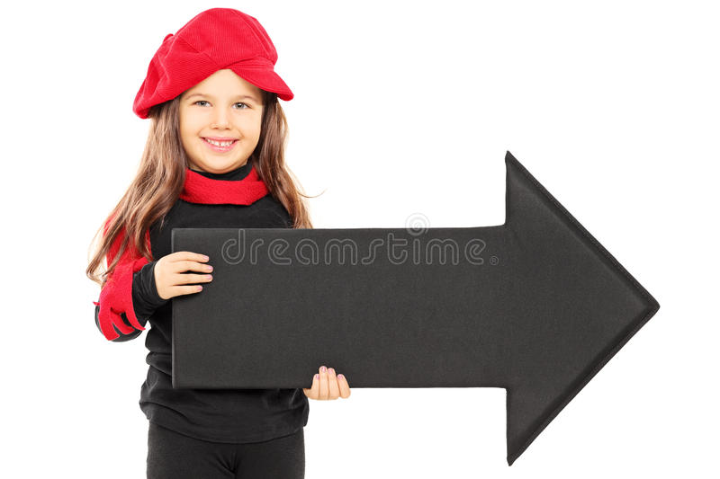 Cute little girl wearing red beret and holding big black arrow p stock image