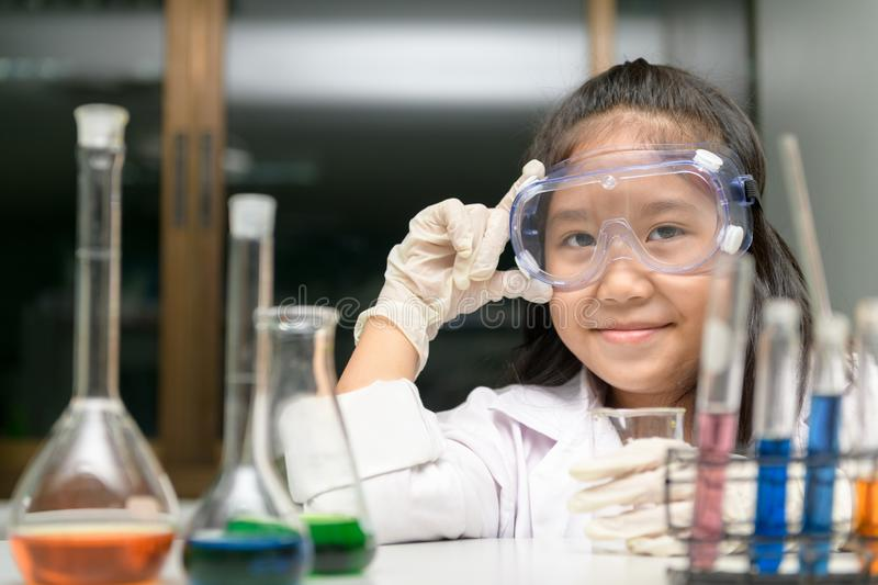 Cute little girl wearing safty goggle and lab coat making experiment royalty free stock photos