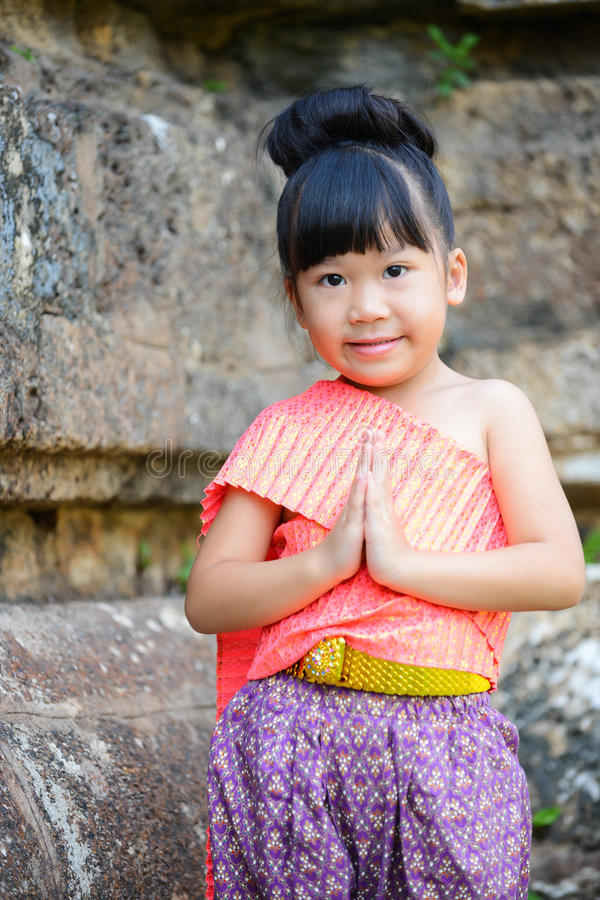 Cute little girl wearing typical thai dress pay respect stock photos