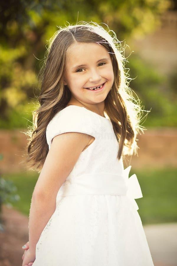 Cute little girl wearing a white dress stock photos