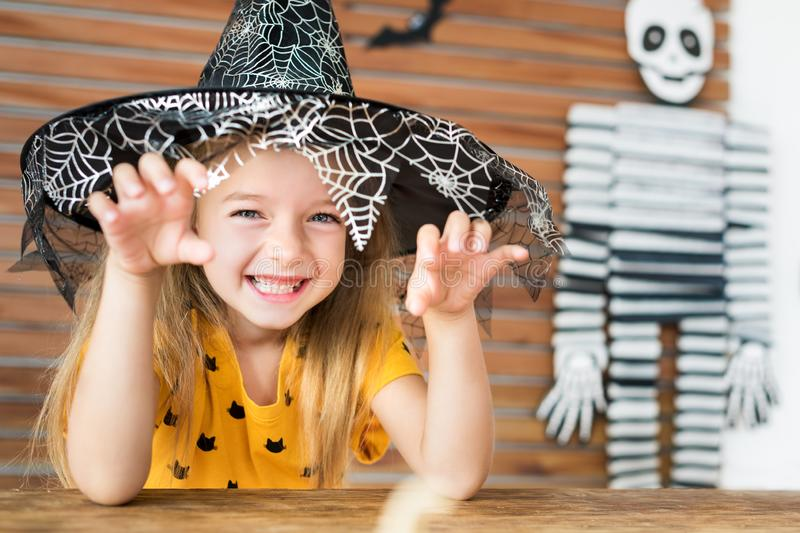 Cute little girl wearing witch hat sitting behind a table in Halloween theme decorated living room, making scary face. royalty free stock image