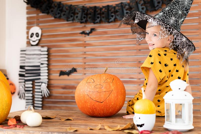 Cute little girl wearing witch hat sitting on a table in Halloween theme decorated room, smiling. Halloween holiday. Cute little girl wearing witch hat sitting royalty free stock image