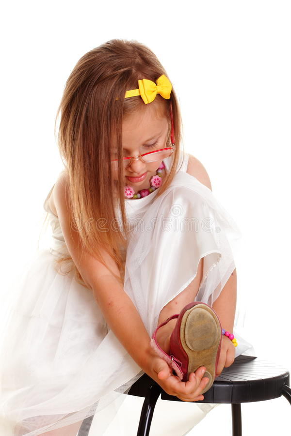 Cute little girl white dress putting on her shoe stock image