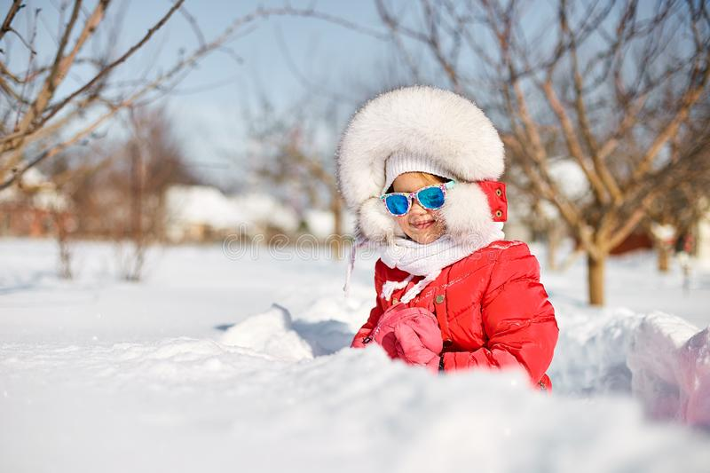 Cute little girl in winter, have fun. And enjoy the fresh snow on a beautiful winter day. Happy laughing toddler girl wearing a red down jacket and white stock photo