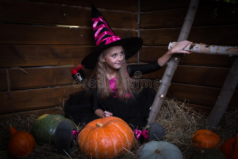 Cute little girl witch. In black dress royalty free stock photography