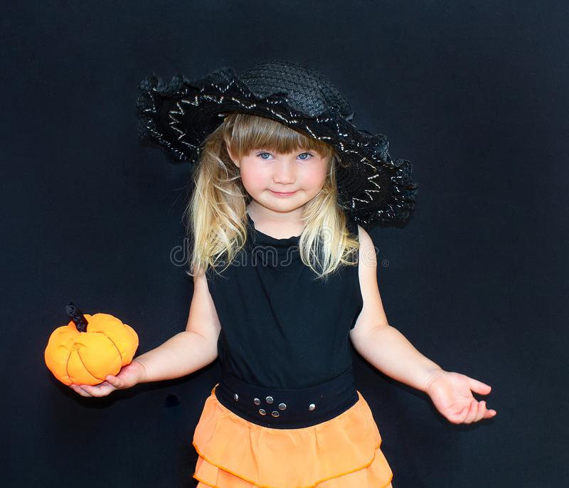 Cute little girl in witch costume with pumpkins. Halloween. On a black background. royalty free stock photos