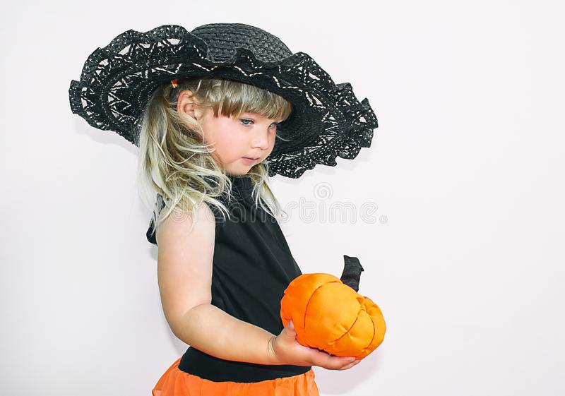 Cute little girl in witch costume with pumpkins. Halloween. On a white background. stock image