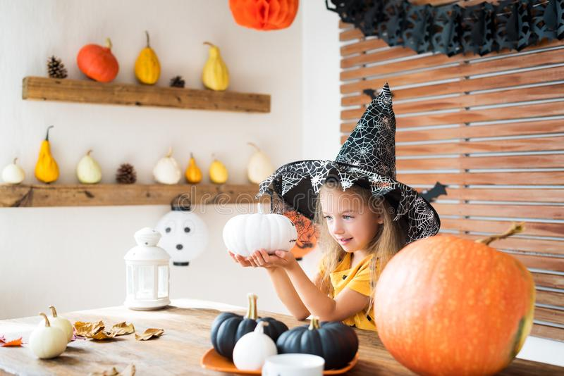 Cute little girl in witch costume sitting behind a table in Halloween theme decorated room, holding hand painted pumpkins smiling. royalty free stock photo