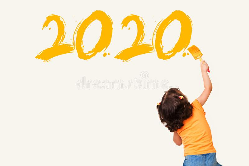 Cute little girl writing new year 2020 with painting brush royalty free stock images