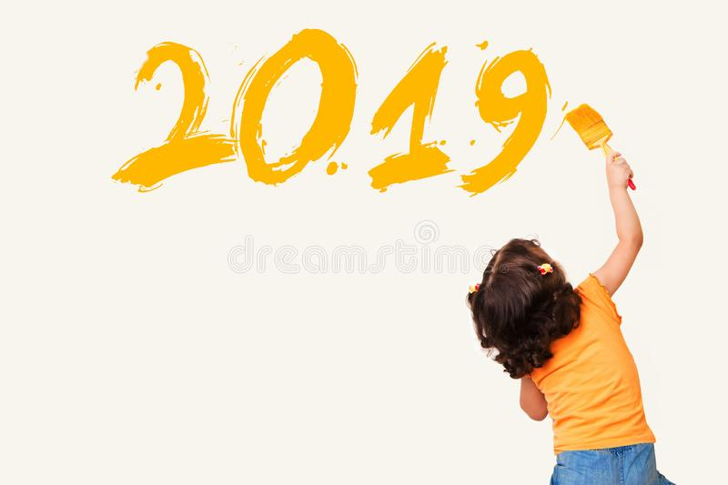 Cute little girl writing new year 2019 with painting brush royalty free stock photography